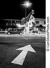 Arrow on pavement and intersection at night in Hanover,...