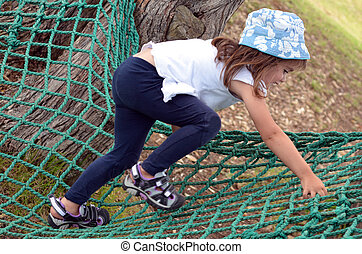 Active child (age 3 - 6 ) with a hat, climb on a net in the...