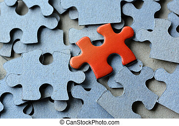 Jigsaw puzzle - Orange puzzle pice standing above the rest...