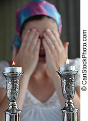 Shabbat eve - Jewish woman says the blessing upon lighting...