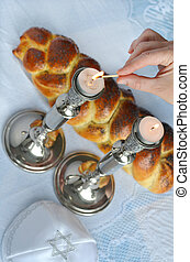 Shabbat eve tableWoman hand lit Shabbath candles with...