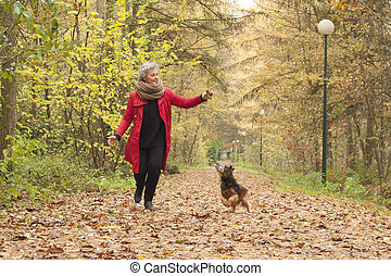 Middle aged lady is playing with her dog - Middle aged woman...