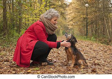 Ager woman and her cute dog in the forest - Middle aged...