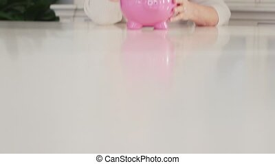Old woman showing piggybank - portrait of happy caucasian...