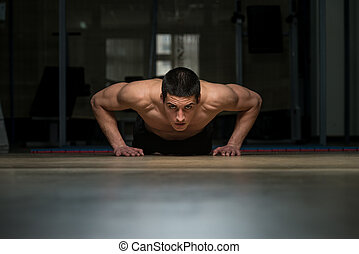 Young Man Doing Press Ups In Gym - Young Athlete Doing...
