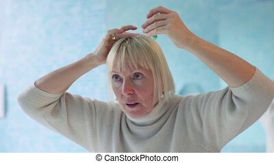 senior woman checking hairline - old caucasian woman...