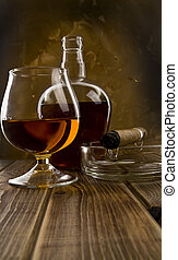 glass and bottle with a cigar on a wooden table