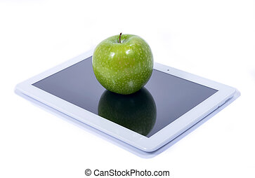Green apple and tablet - Green apple placed on the screen of...