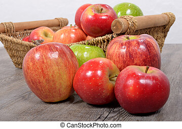 different apples in a wicker basket on wood table