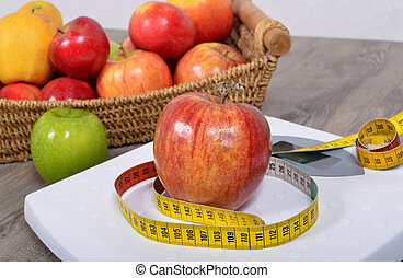 Apple placed on a scales, - Apple placed on a scales and...