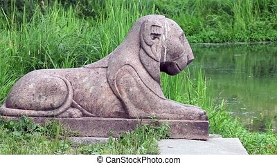 stone lion sculpture on the shore of pond zoom in