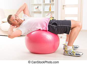 Handsome man doing sit ups on the ball