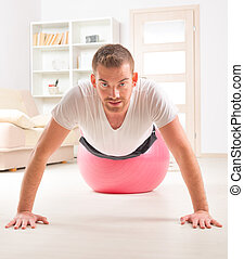 Handsome man doing push ups on the gym ball