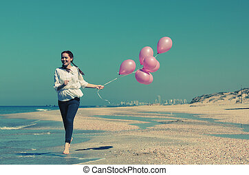 Young woman walking on the beach with pink balloons. Photo...