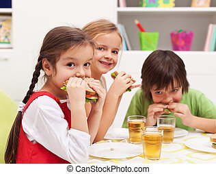 Kids chomping on sandwiches - Three kids chomping on healthy...