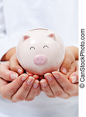 Cute small piggy bank in child hands