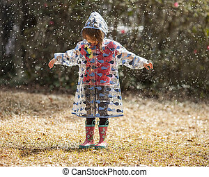little girl playing in the rain - little girl in raincoat...