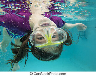 little girl swimming underwater having fun - little girl...
