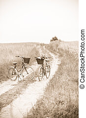 Two old style looking bikes parked on dirt road, sepia. -...