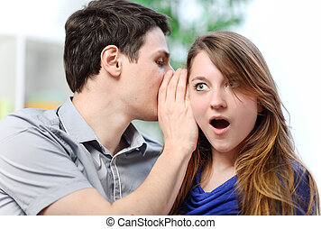 man whispering in the ear of his surprised wife