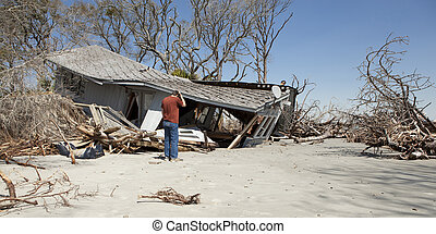 man grieving over destroyed house - man grieving over flood...