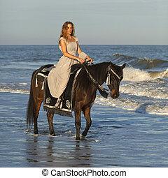 woman on horseback in ocean - woman in medieval dress on...