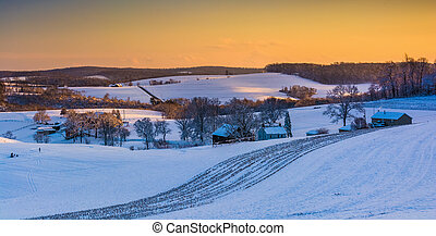 View of snow covered rolling hills and farm fields at sunset...