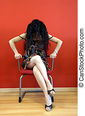Seductive pose - Young woman sitting on a chair and looking...