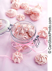 Pink meringues in a glass jar on pastel background