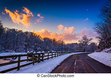 Winter sunset over a fence and country road in rural York County, Pennsylvania.