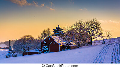 Winter view of a barn on a snow covered farm field at...