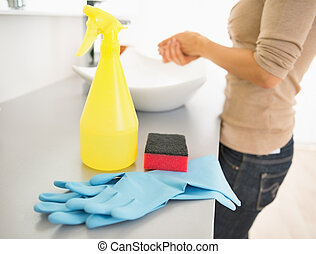 Closeup on sponge; gloves and spray bottle on desk and...