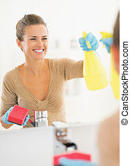 Smiling young housewife cleaning mirror in bathroom