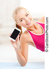 smiling woman lying on the floor with smartphone - fitness,...