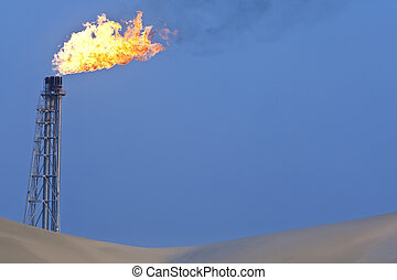 Gas Burning - A flare stack burning off excess gas at an oil...