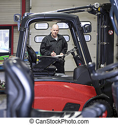 Forklift Mechanic with clip board - An experienced, and...