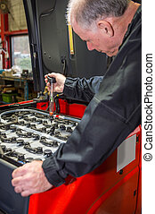Mechanic tests the battery acid - Mechanic is measuring the...