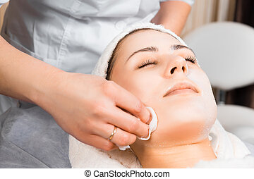 skin care, medical beautician removes the mask from the face...