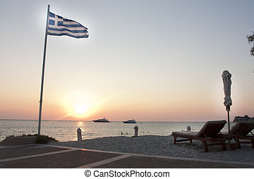 sunset on a greek beach with yachts in distance - super...