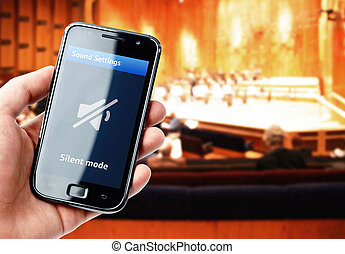 Hand holding smartphone with mute sound during concert -...