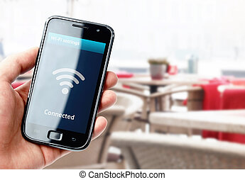 Hand holding smartphone with wi-fi connection in cafe - Hand...