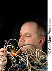 Man Tangled in Wires - A man tangled up in wires and cables.