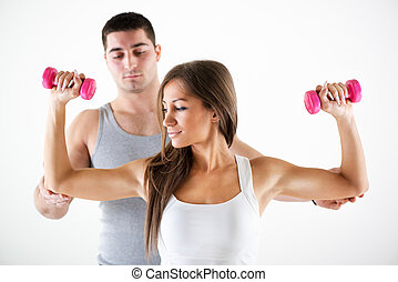 Personal trainer assisting a client - Young beautiful woman...