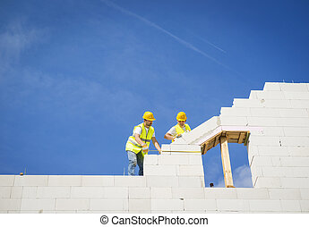 House construction - Builders are working on the top of...