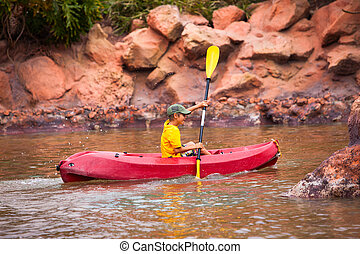 Happy boy paddling kayak on the river and enjoying a lovely...