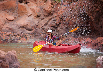 Happy little girl on a kayak on a river at summer