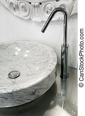 Marble sink and the metal tap in a bathroom
