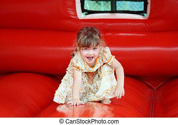 Little beautiful girl in dress plays in red bouncy castle...