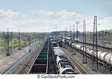 Many long freight trains at railway station with many wires