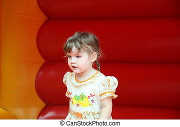 Little beautiful happy girl jumps on red bouncy castle and...